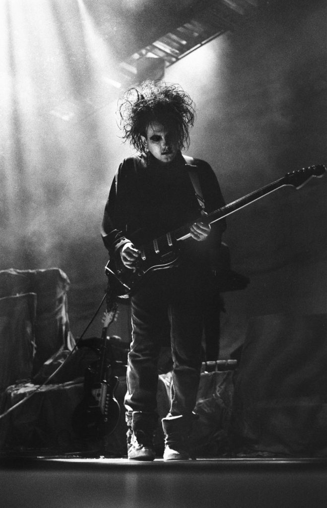 The Cure's Robert Smith playing his guitar in 1989. Photo by Jason Scott Tilley